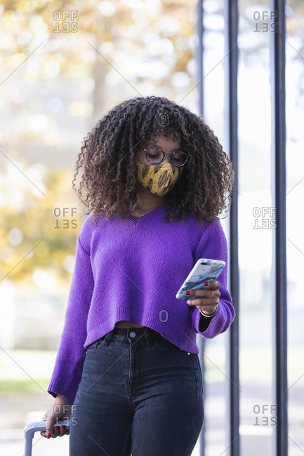 Fashionable young woman using mobile phone while walking with luggage during COVID-19