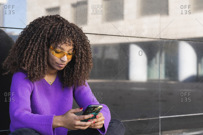 Afro woman wearing sunglasses using smart phone against wall