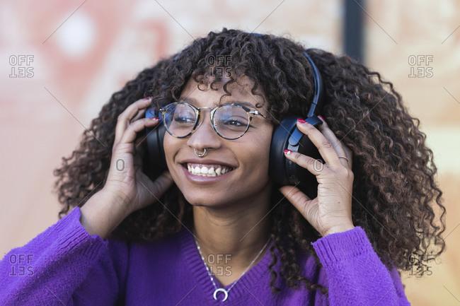 Smiling woman enjoying music through headphones
