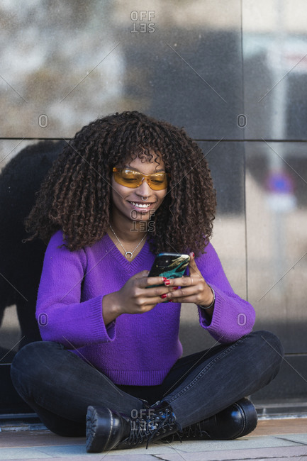 Smiling woman sitting on sidewalk while using mobile phone against wall