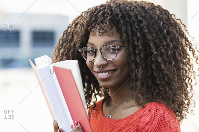 Smiling young woman with curly hair holding book