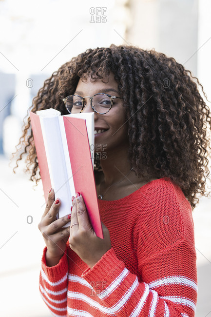 Happy young woman in warm clothes covering face with book