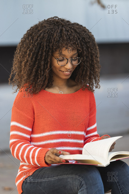 Smiling woman in red sweater reading book