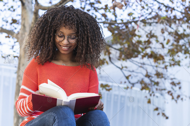 Happy afro woman reading book against tree