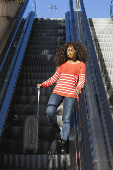 Afro young woman with wheeled luggage moving up on escalator during COVID-19