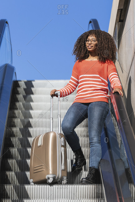 Smiling young woman with wheeled luggage day dreaming while moving up on escalator
