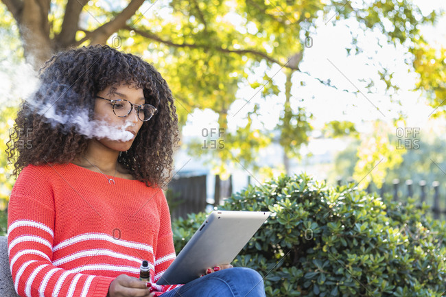Young woman using digital tablet while smoking electronic cigarette at public park
