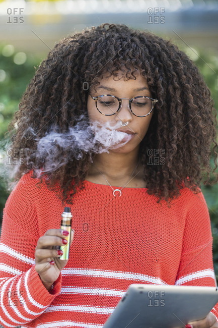 Afro woman wearing glasses smoking electronic cigarette while using digital tablet at park