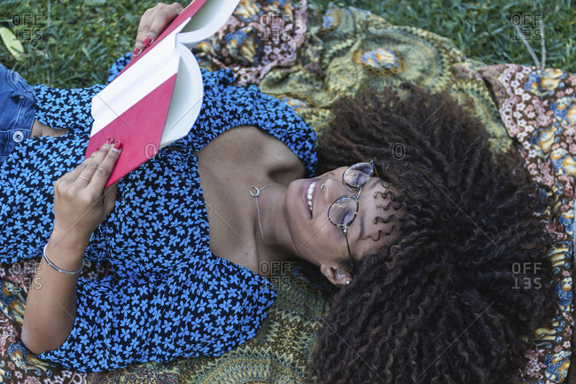 Happy young woman lying on blanket while reading book in public park