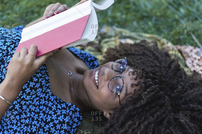 Smiling young woman with curly hair lying down while holding book at public park