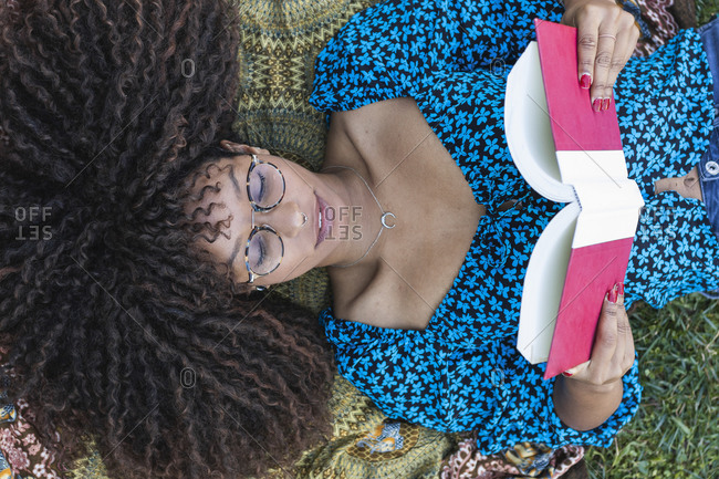 Afro young woman with curly hair reading book while lying down at public park