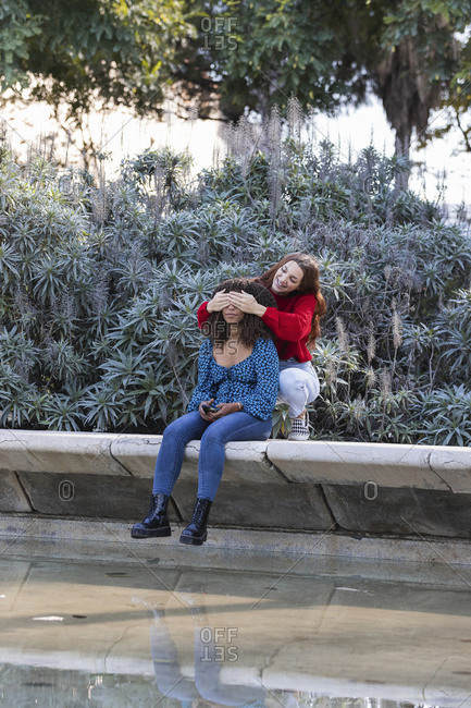Smiling young woman covering eyes of girlfriend while sitting on retaining wall in public park