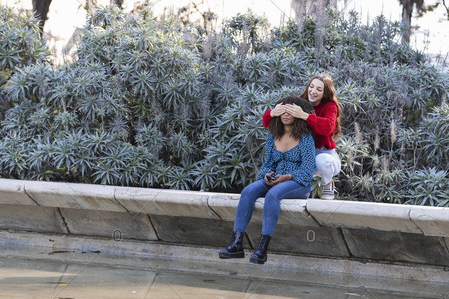 Young woman covering eyes of girlfriend in public park