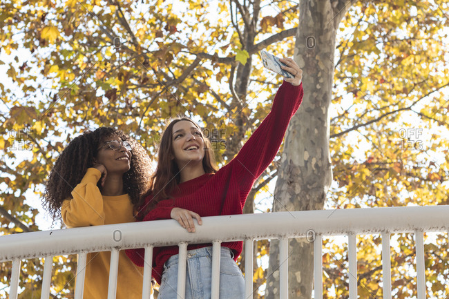 Multi ethnic young women taking selfie while standing by railing at public park
