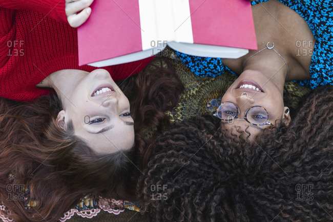 Smiling young women reading book together while on blanket at public park