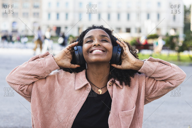 Smiling young with eyes closed listening music through headphones in city