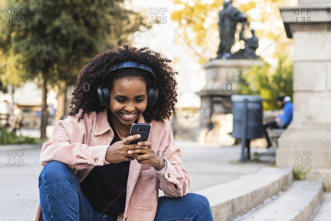 Happy afro young woman using mobile phone while listening music on staircase in city