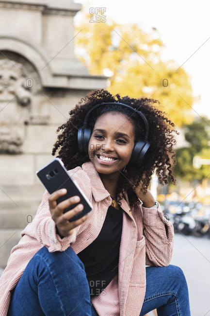 Smiling fashionable young woman taking selfie while listening music in city