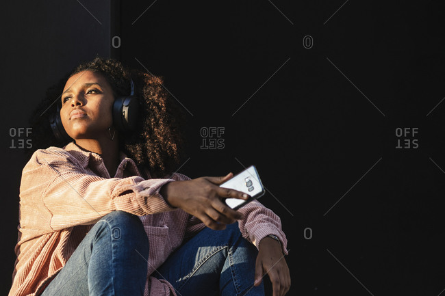Young woman with mobile phone day dreaming against black wall on sunny day