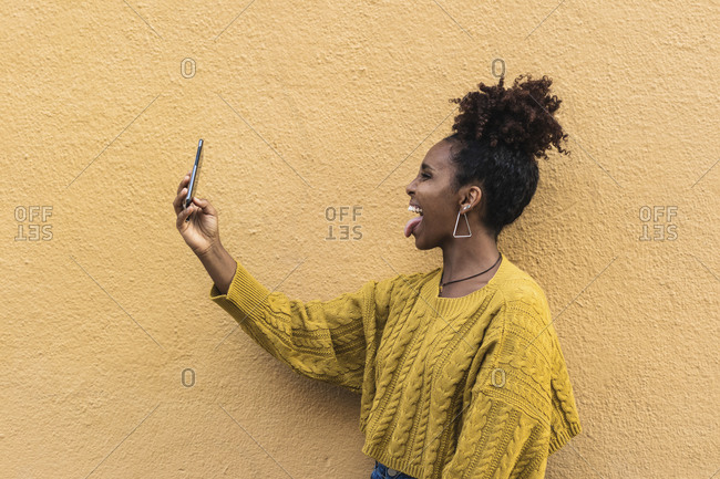 Happy afro woman sticking out tongue while taking selfie by yellow wall