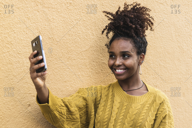Smiling young woman taking selfie through mobile phone by yellow wall