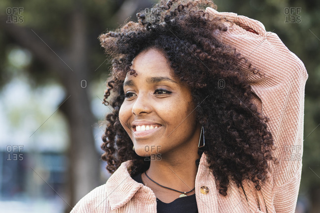 Smiling young woman with hand in hair looking away in city