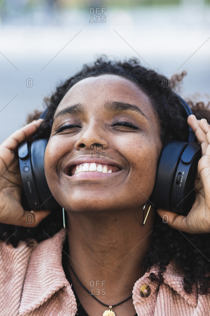 Happy afro woman with eyes closed listening music through headphones in city