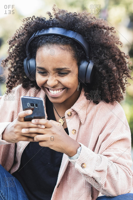 Cheerful young woman listening music while using mobile phone in city