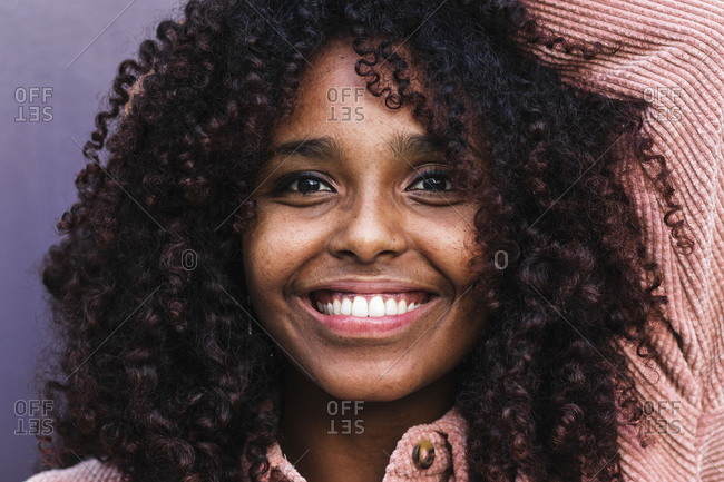 Happy afro young woman with curly hair against wall