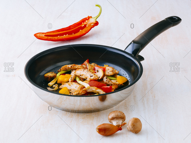Fried chicken breast with mushrooms and vegetables on frying pan