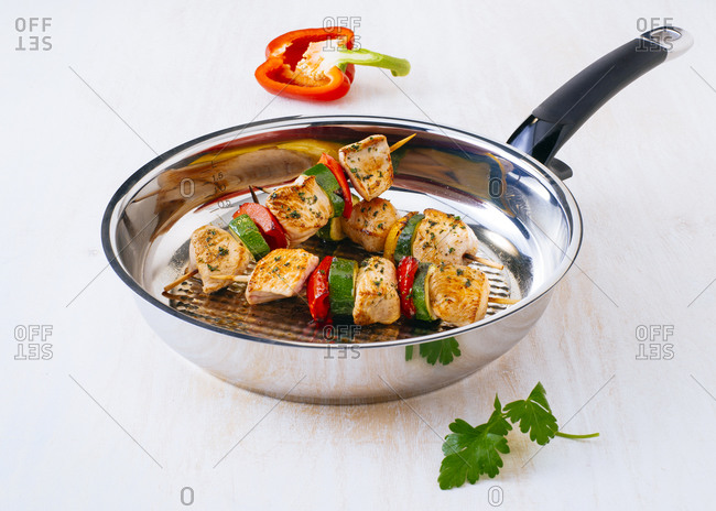 Fried chicken skewers with vegetables on frying pan