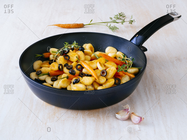 Frying pan of Italian gnocchi with olives and carrots