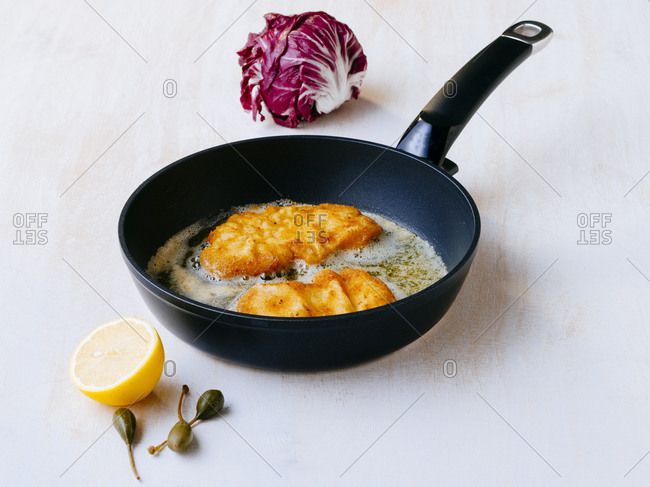 Wiener schnitzel frying on frying pan