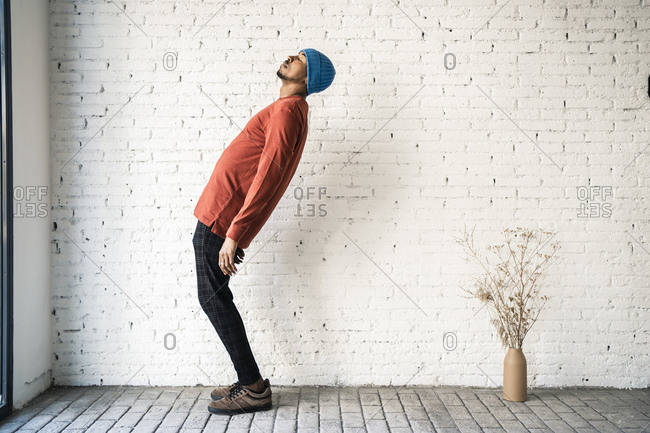 Man with eyes closed bending backwards against white brick wall