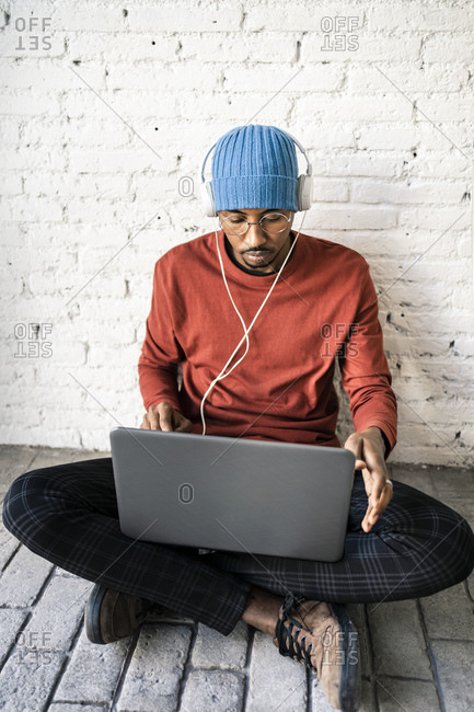 Freelance worker using laptop while listening music through headphones against brick wall