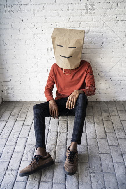 Man wearing brown paper bag on head against white brick wall