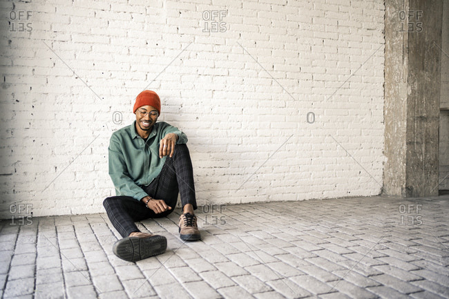 Happy man in knit hat sitting on floor against white brick wall
