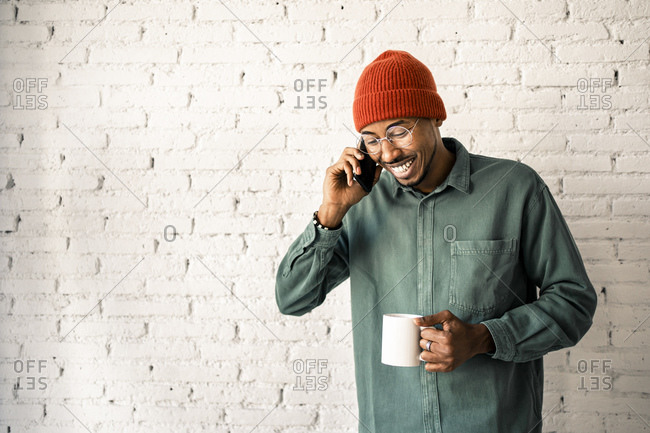 Smiling man wearing knit hat on phone call holding coffee cup against white brick wall