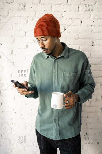 Mid adult man having coffee while using mobile phone against white brick wall