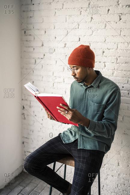 Man wearing eyeglasses reading book against white brick wall