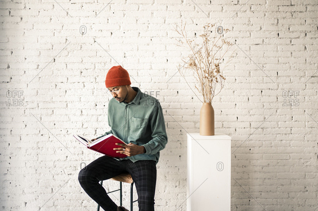 Man in knit hat reading book by dried plant vase against white brick wall