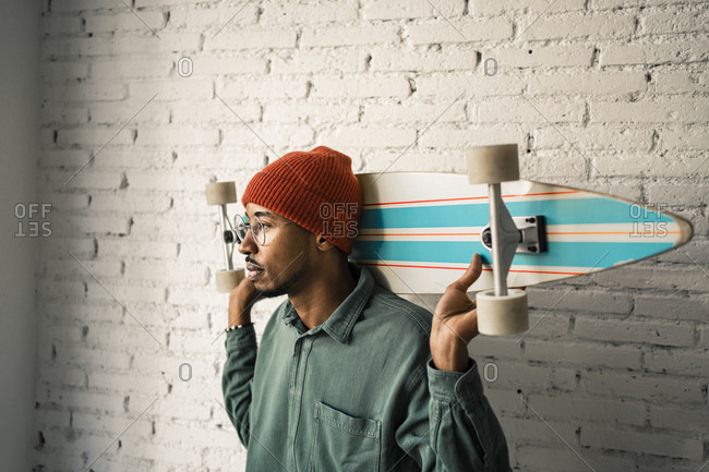 Man with skateboard day dreaming against white brick wall