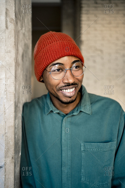 Smiling man wearing knit hat day dreaming while leaning on wall