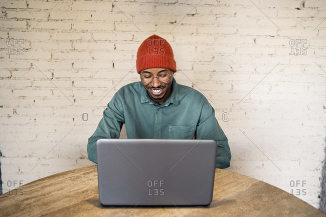 Happy male professional using laptop on table against white brick wall
