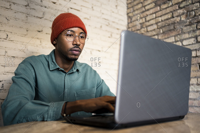 Businessman working on laptop against brick wall at table
