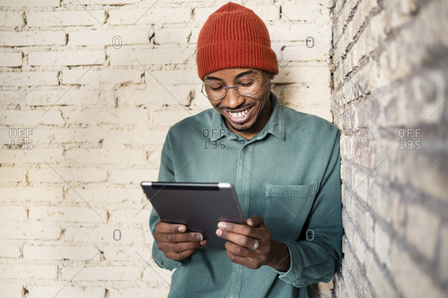 Happy man using digital tablet while leaning by brick wall