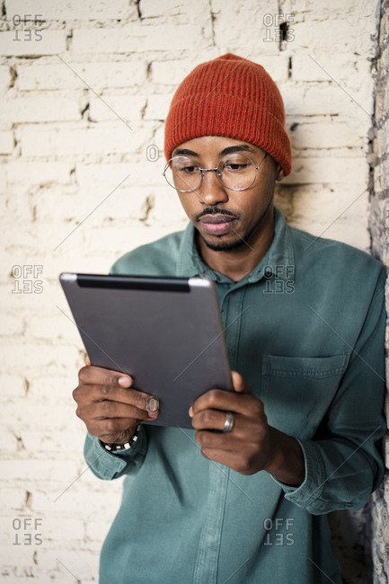 Mid adult man using digital tablet while leaning by brick wall