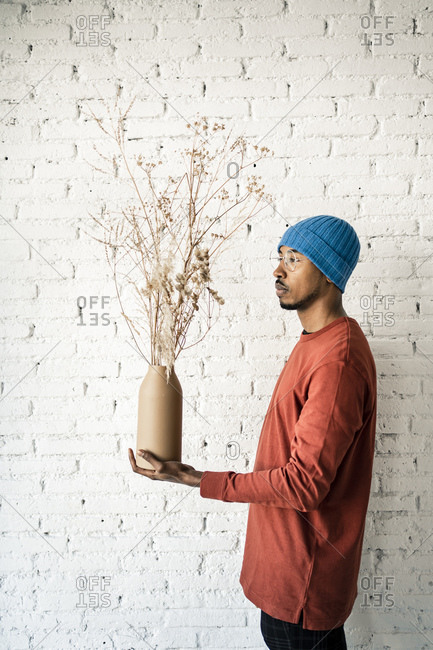 Man holding dried plant vase white standing by brick wall