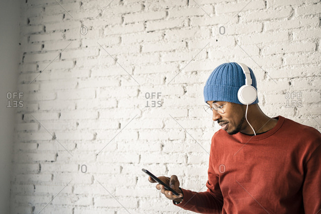 Smiling man using mobile phone while listening music through headphones against white brick wall