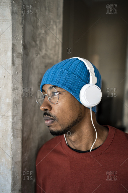 Man listening music through headphones while day dreaming by wall